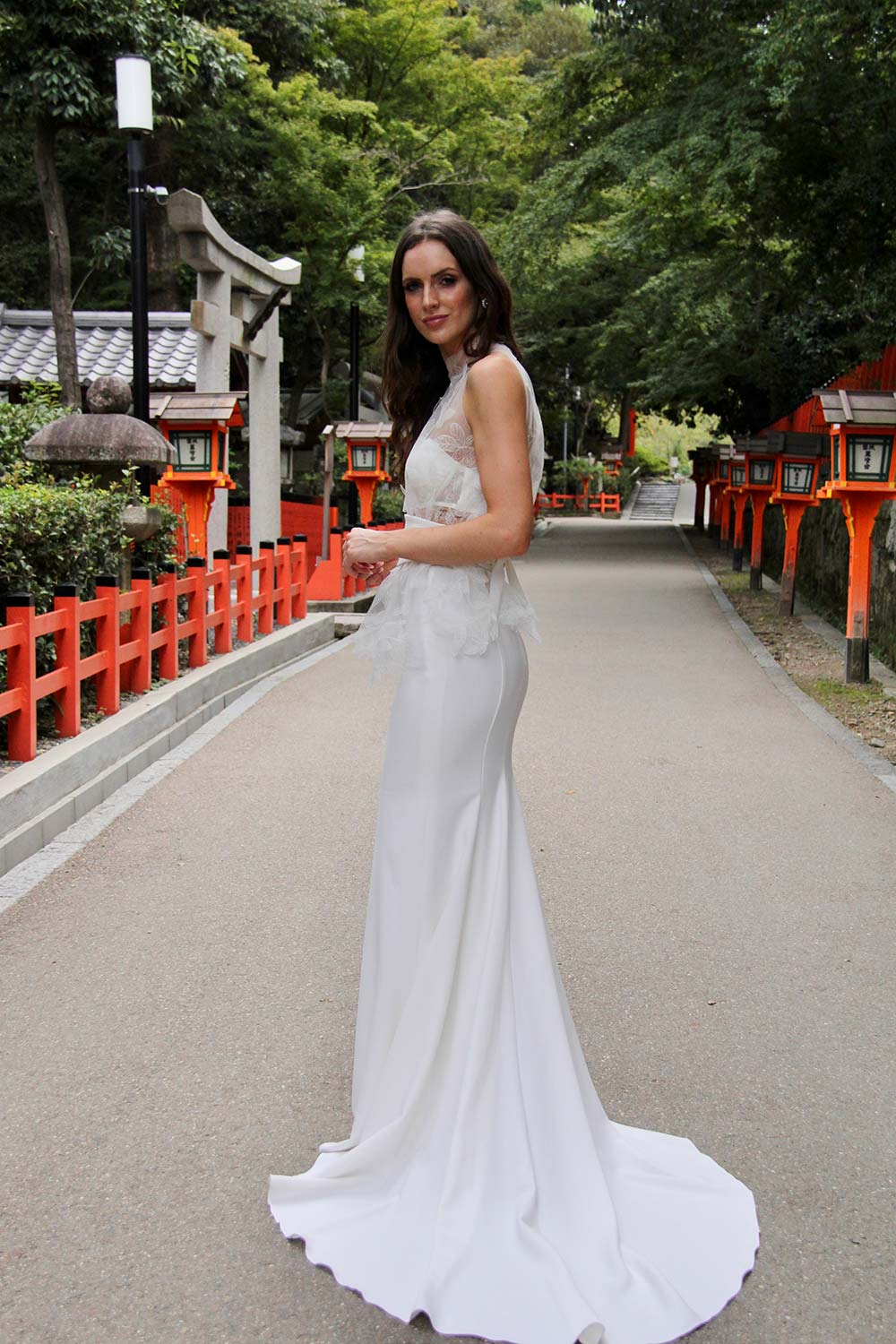 Female model wearing Vinka Design An Oriental Affair Wedding Dress. Standing in a gothic doorway the side detail of gown with a high necked delicately hand-embroidered leaf lace cinched in at the waist with a wide kimono belt with skirt