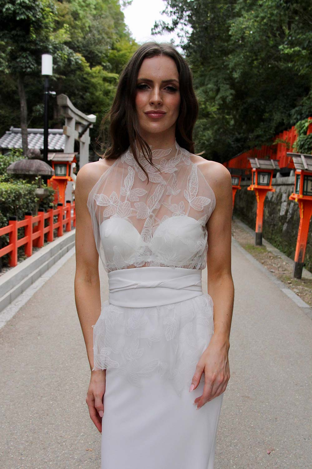 Female model wearing Vinka Design An Oriental Affair Wedding Dress. Standing in a gothic doorway the front detail of gown with a high necked delicately hand-embroidered leaf lace cinched in at the waist with a wide kimono belt with skirt