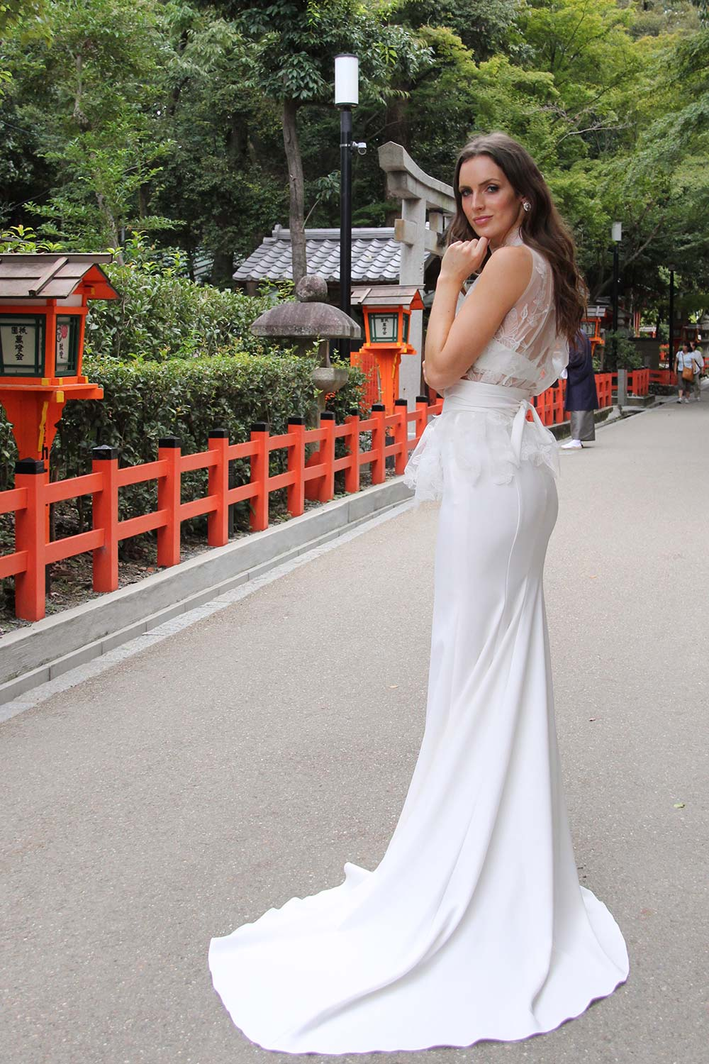 Female model wearing Vinka Design An Oriental Affair Wedding Dress. Standing in a gothic doorway the back detail of gown with a high necked delicately hand-embroidered leaf lace cinched in at the waist with a wide kimono belt with skirt