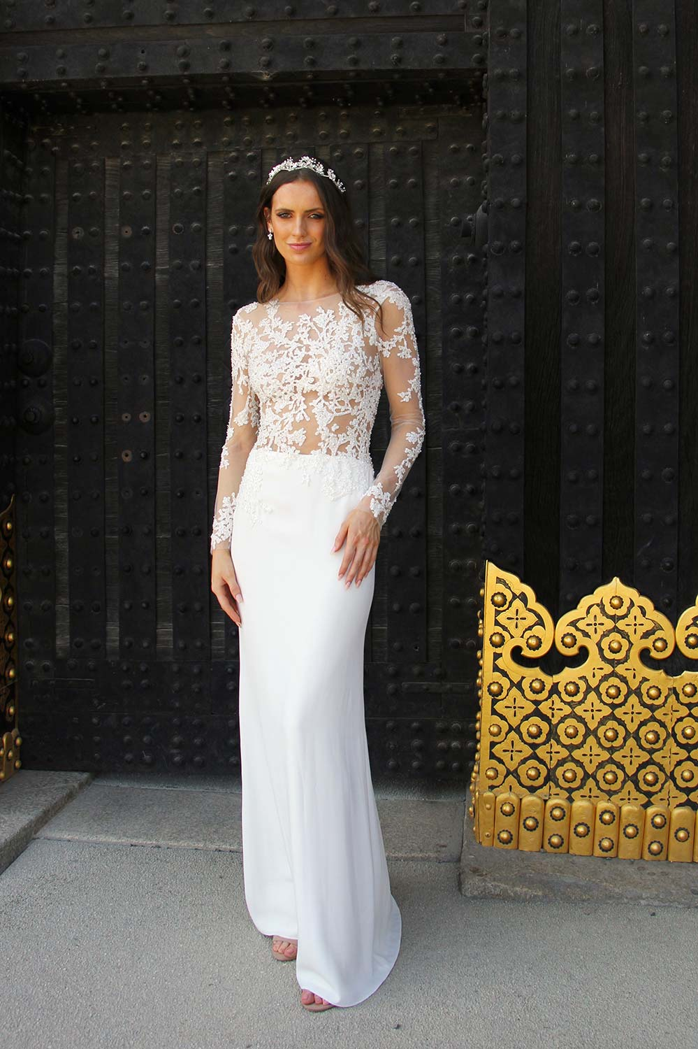 Female model wearing Vinka Design An Oriental Affair Wedding Dress. Standing in a gothic doorway the front detail of gown with a high neckline and a daringly low back and a flattering floor-length detachable skirt