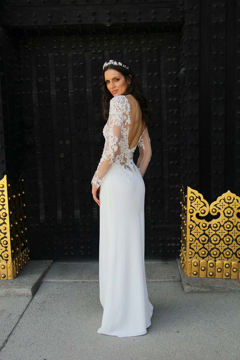 Female model wearing Vinka Design An Oriental Affair Wedding Dress. Standing in a gothic doorway the back detail of gown with a high neckline and a daringly low back and a flattering floor-length detachable skirt