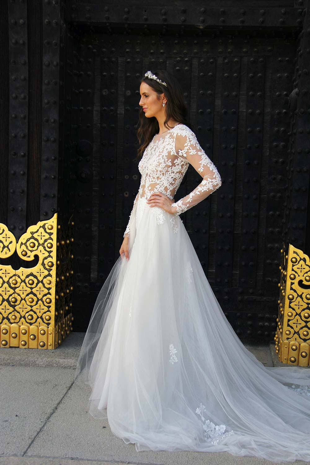 Female model wearing Vinka Design An Oriental Affair Wedding Dress. Standing in a gothic doorway the side detail of gown with a high neckline and a daringly low back and a flattering floor-length detachable skirt
