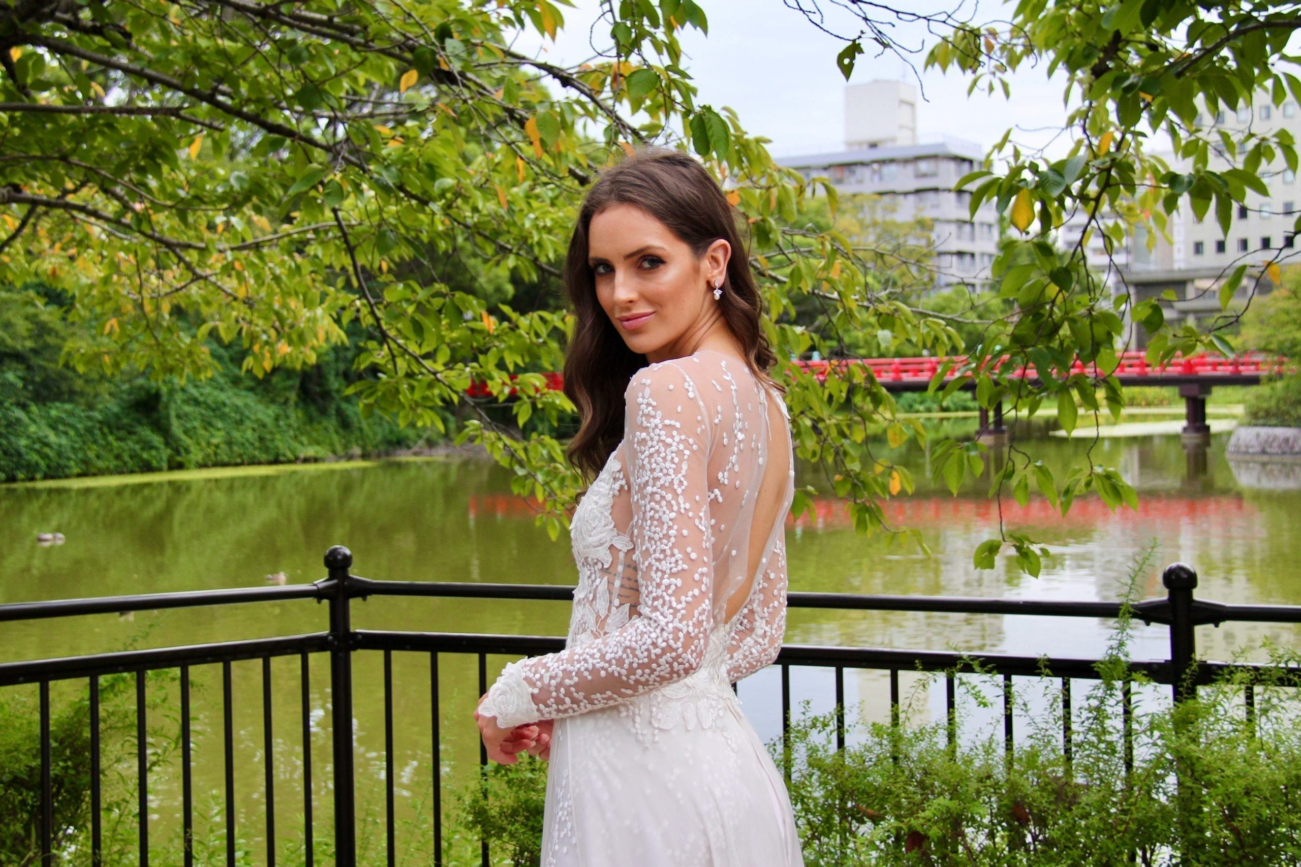 Female model wearing Vinka Design An Oriental Affair Wedding Dress. In a quiet japanese garden the back detail of gown with a fitted tulle-based bodice with Itallian embroidered roses with a skirt that features the beautiful spotted embroidery and flowing silk chiffon.