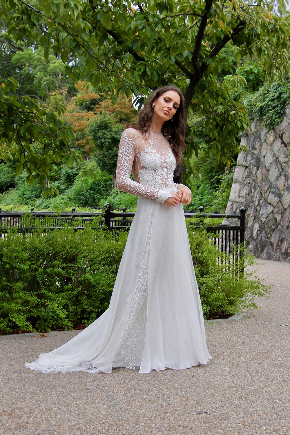 Female model wearing Vinka Design An Oriental Affair Wedding Dress. In a quiet japanese garden the front detail of gown with a fitted tulle-based bodice with Itallian embroidered roses with a skirt that features the beautiful spotted embroidery and flowing silk chiffon.