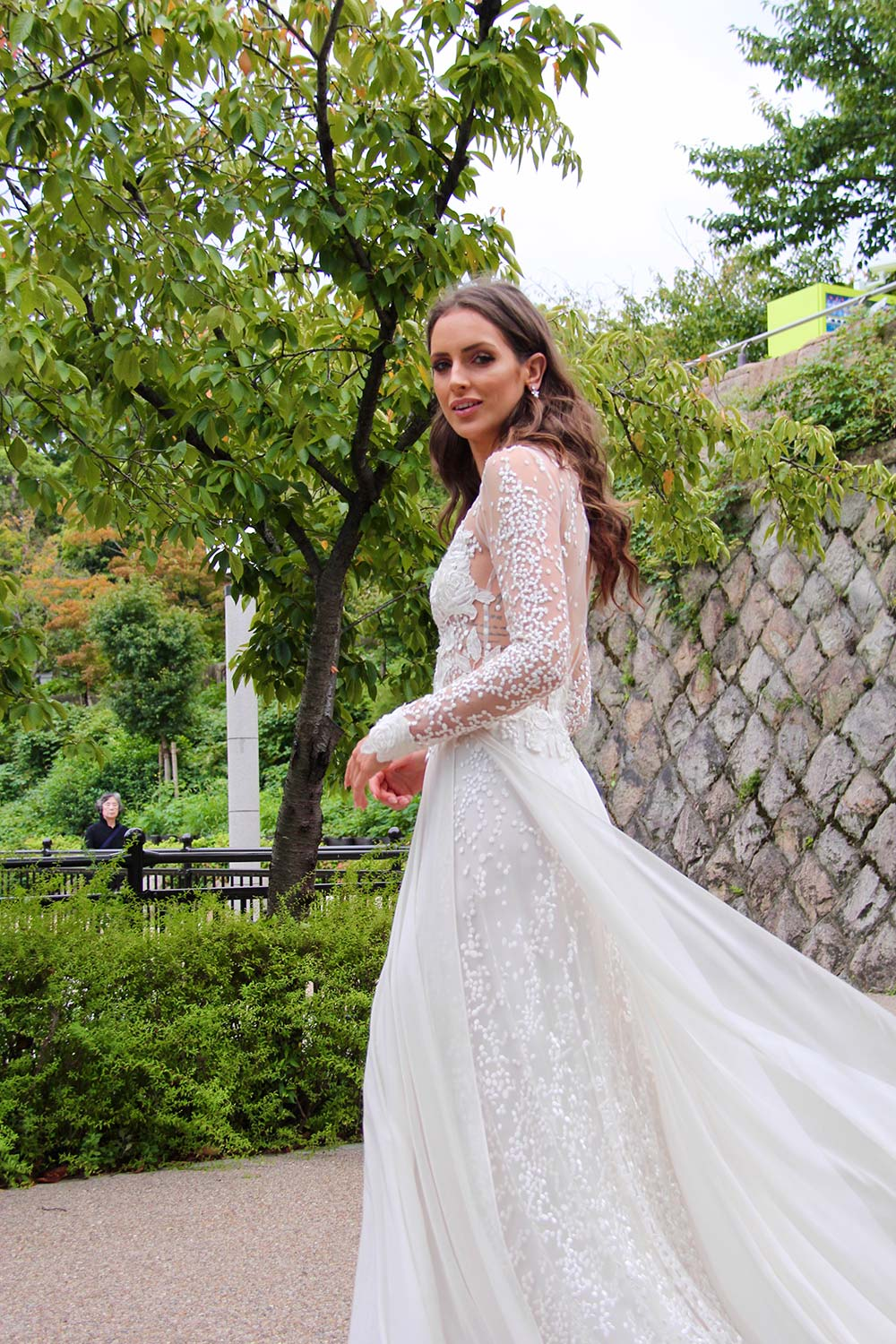 Female model wearing Vinka Design An Oriental Affair Wedding Dress. In a quiet japanese garden the side detail of gown with a fitted tulle-based bodice with Itallian embroidered roses with a skirt that features the beautiful spotted embroidery and flowing silk chiffon.