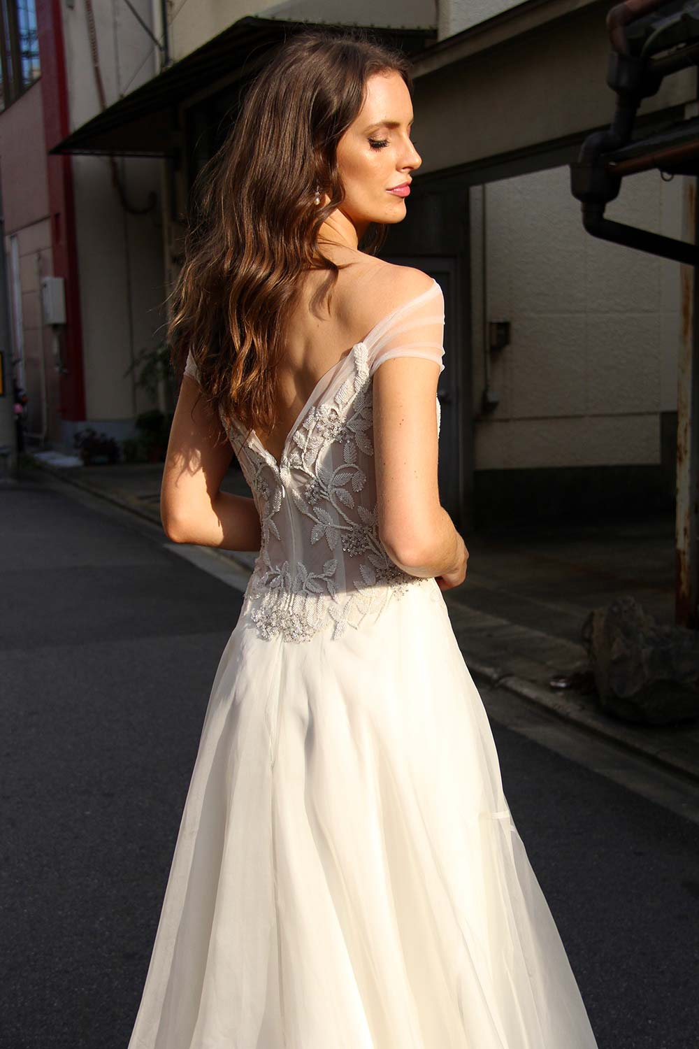 Female model wearing Vinka Design An Oriental Affair Wedding Dress. In a quiet japanese street the back detail of a boned, structured, semi-sheer bodice and a skirt made of soft silk organza.