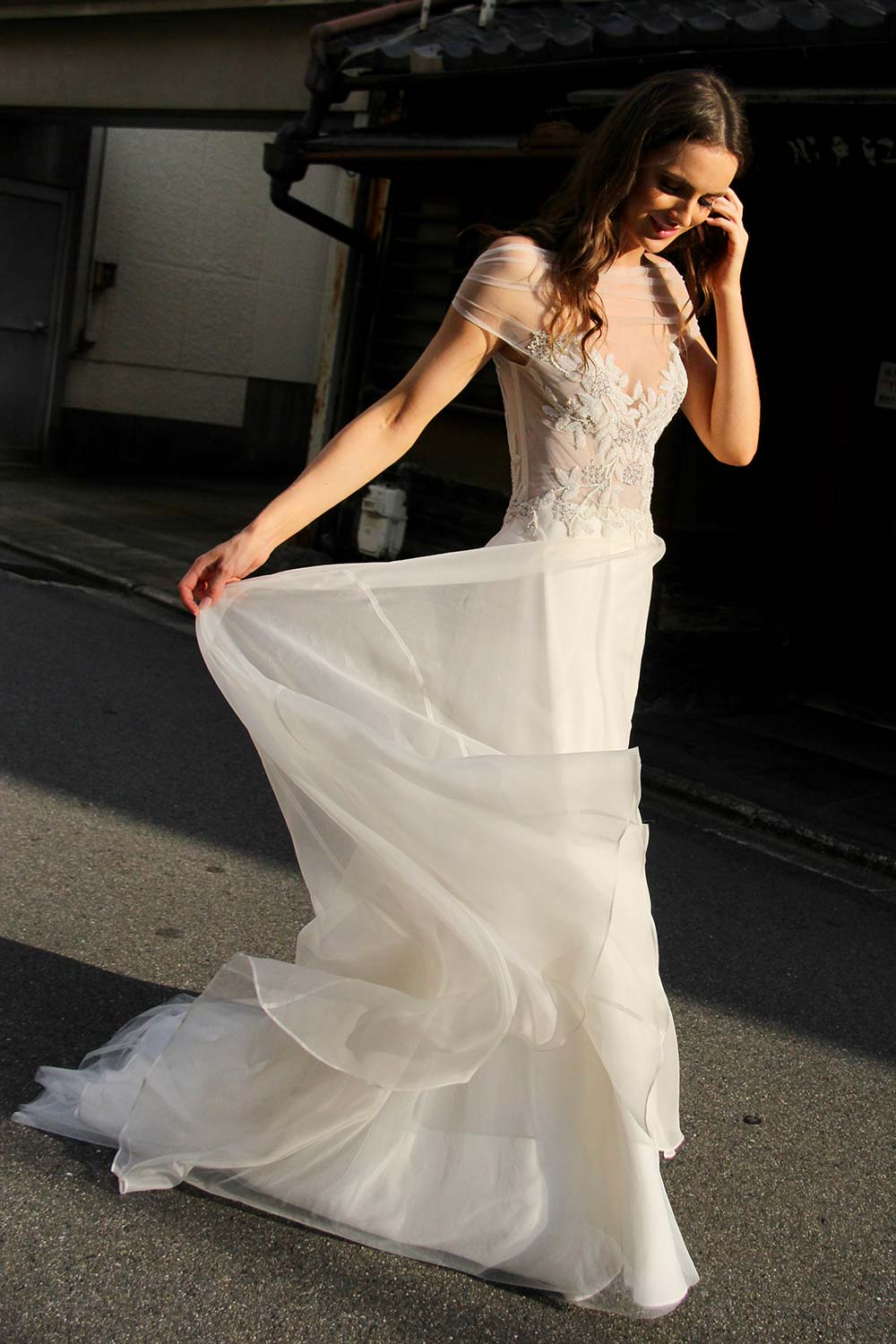 Female model wearing Vinka Design An Oriental Affair Wedding Dress. In a quiet japanese street the side detail of a boned, structured, semi-sheer bodice and a skirt made of soft silk organza.