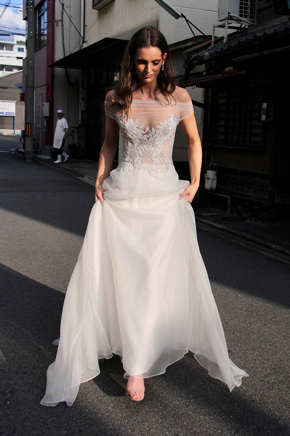 Female model wearing Vinka Design An Oriental Affair Wedding Dress. In a quiet japanese street the front detail of a boned, structured, semi-sheer bodice and a skirt made of soft silk organza.