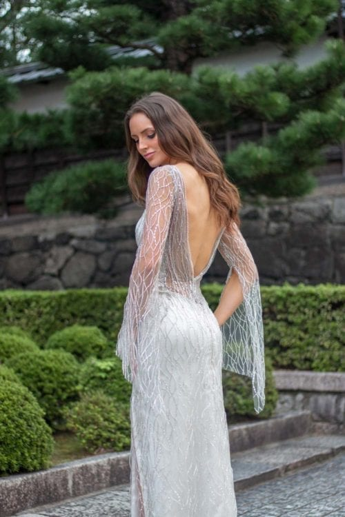 Female model wearing Vinka Design An Oriental Affair Wedding Dress. In a japanese garden the back detail of a high sheer neckline with a daringly low beaded back and a form-fitting skirt, floor length with a side split.