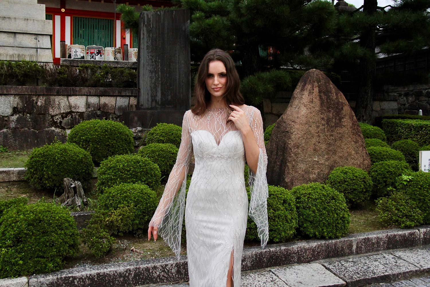 Female model wearing Vinka Design An Oriental Affair Wedding Dress. In a japanese garden the front detail of a high sheer neckline with a daringly low beaded back and a form-fitting skirt, floor length with a side split.