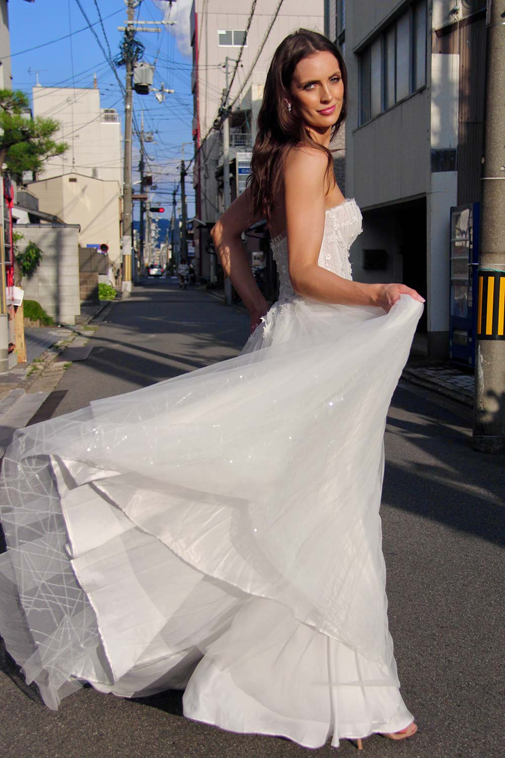 Female model wearing Vinka Design An Oriental Affair Wedding Dress. On a japanese street the side detail of a semi-sheer bodice with boning and hand-appliqued lace and skirt made with multiple layers of tulle