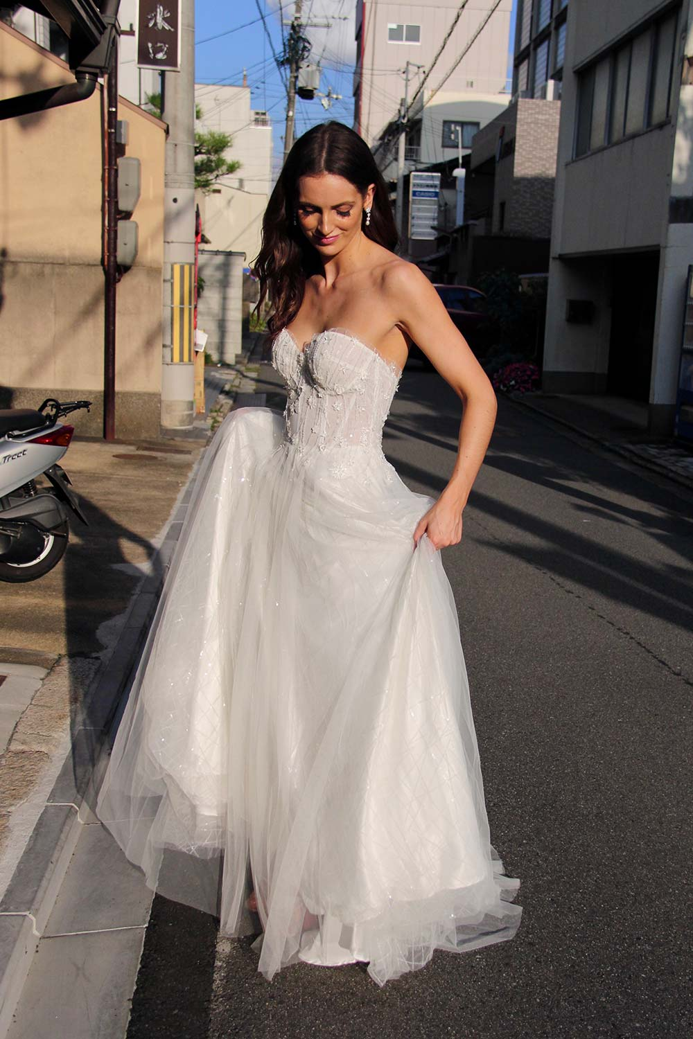Female model wearing Vinka Design An Oriental Affair Wedding Dress. On a japanese street the front detail of a semi-sheer bodice with boning and hand-appliqued lace and skirt made with multiple layers of tulle