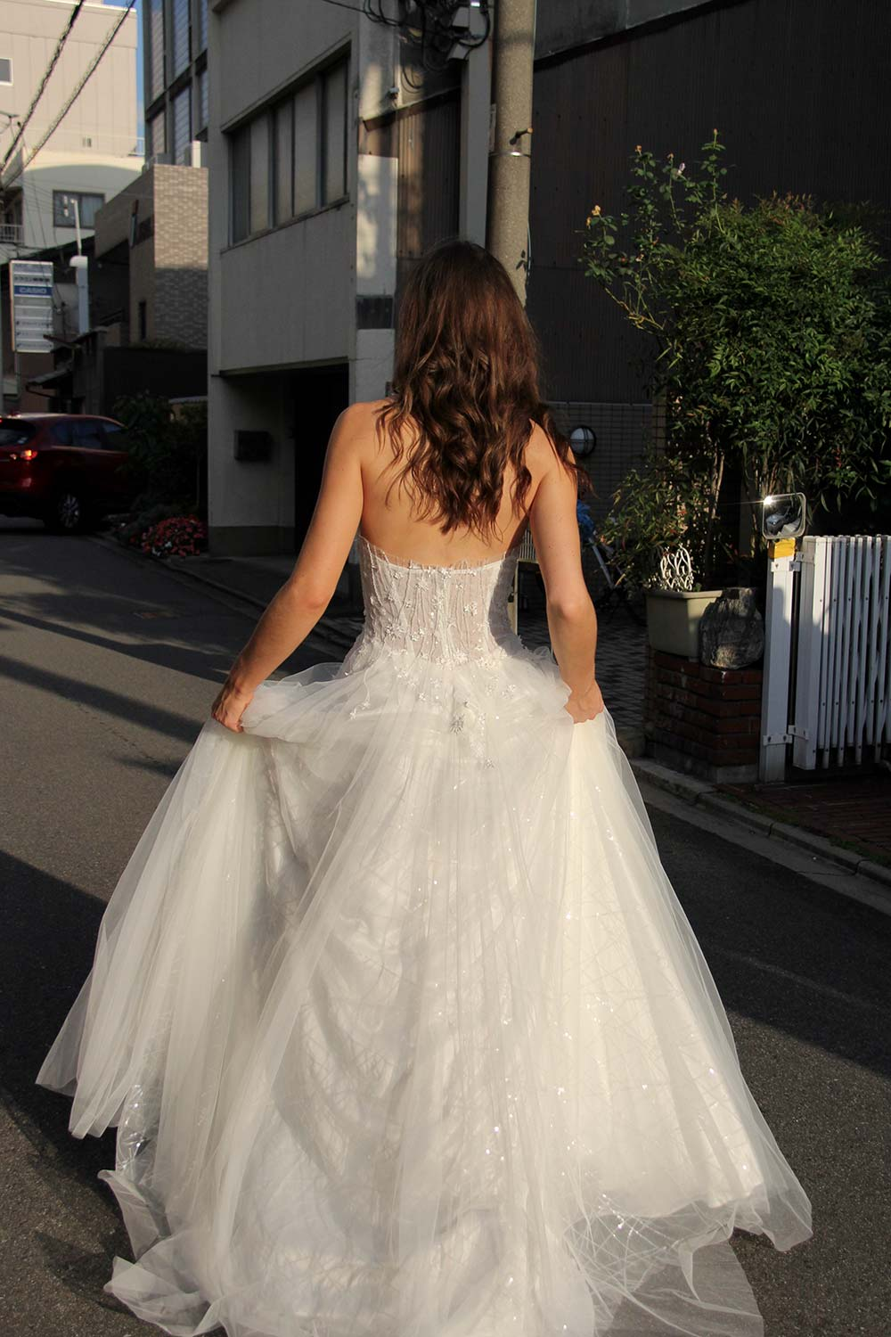 Female model wearing Vinka Design An Oriental Affair Wedding Dress. On a japanese street the back detail of a semi-sheer bodice with boning and hand-appliqued lace and skirt made with multiple layers of tulle