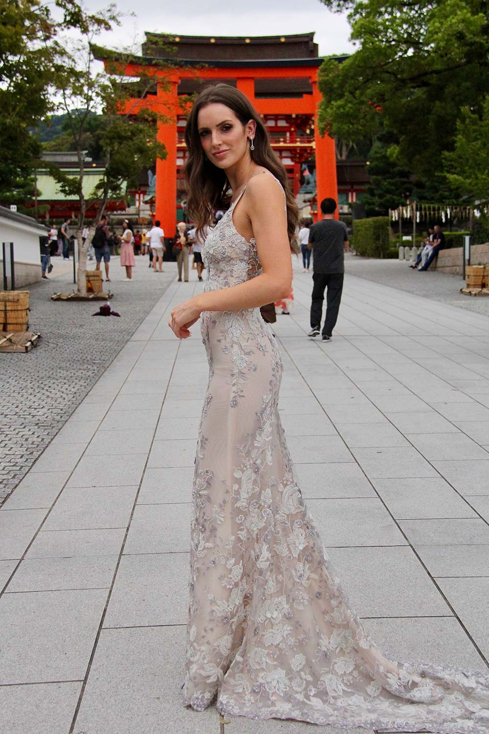 Female model wearing Vinka Design An Oriental Affair Wedding Dress. At a japanese temple in Kyoto the side detail of a slender silhouette form-fitting gown with a low sheer back, deep v-neckline and thin straps