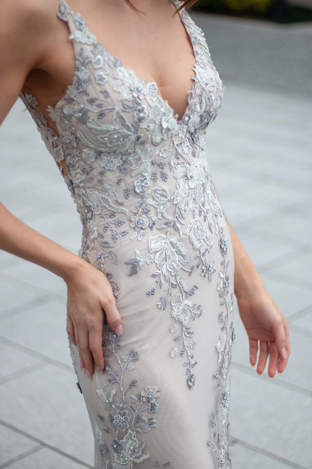 Female model wearing Vinka Design An Oriental Affair Wedding Dress. At a japanese temple in Kyoto the front detail of a slender silhouette form-fitting gown with a low sheer back, deep v-neckline and thin straps