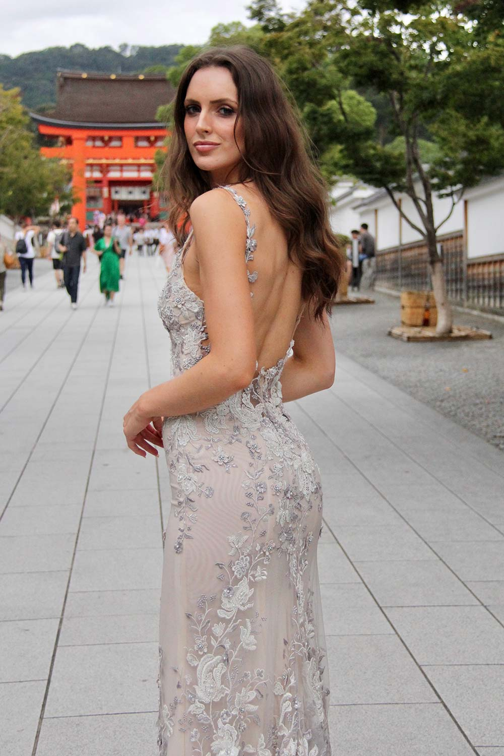 Female model wearing Vinka Design An Oriental Affair Wedding Dress. At a japanese temple in Kyoto the back detail of a slender silhouette form-fitting gown with a low sheer back, deep v-neckline and thin straps