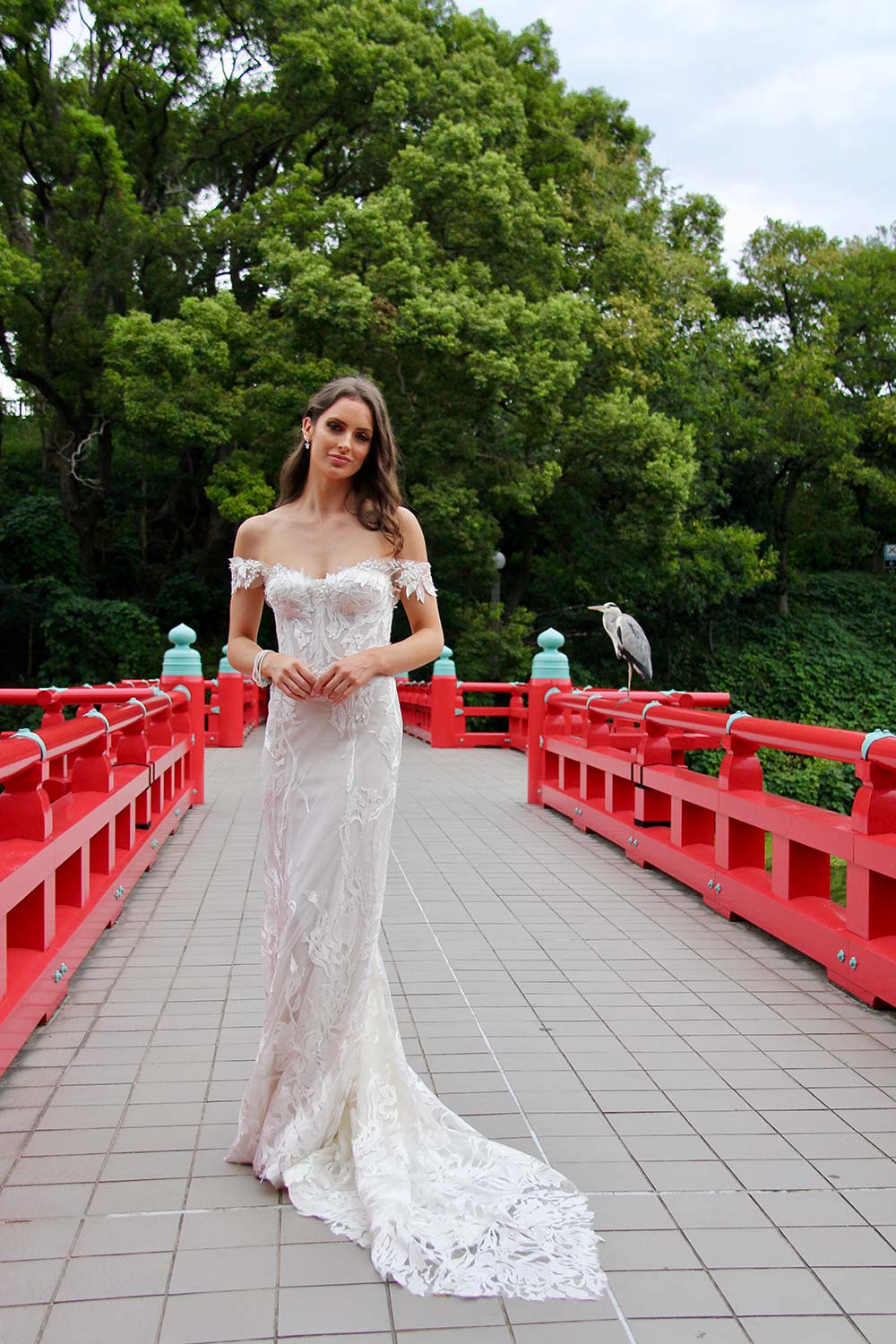 Female model wearing Vinka Design An Oriental Affair Wedding Dress. On a japanese bridge the front detail of a off-shoulder and form-fitting gown with corset-like boning.