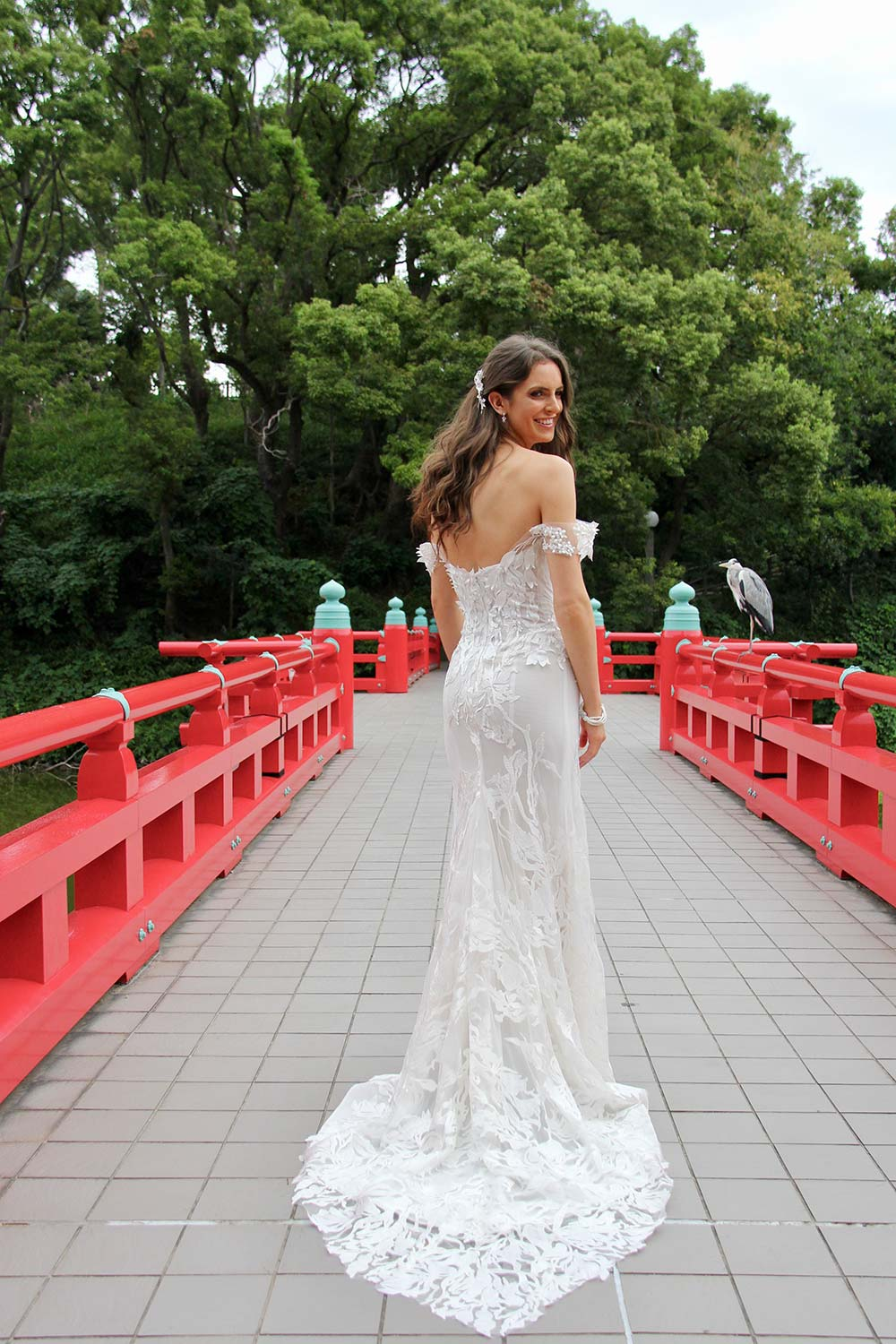 Female model wearing Vinka Design An Oriental Affair Wedding Dress. On a japanese bridge the back detail of a off-shoulder and form-fitting gown with corset-like boning.