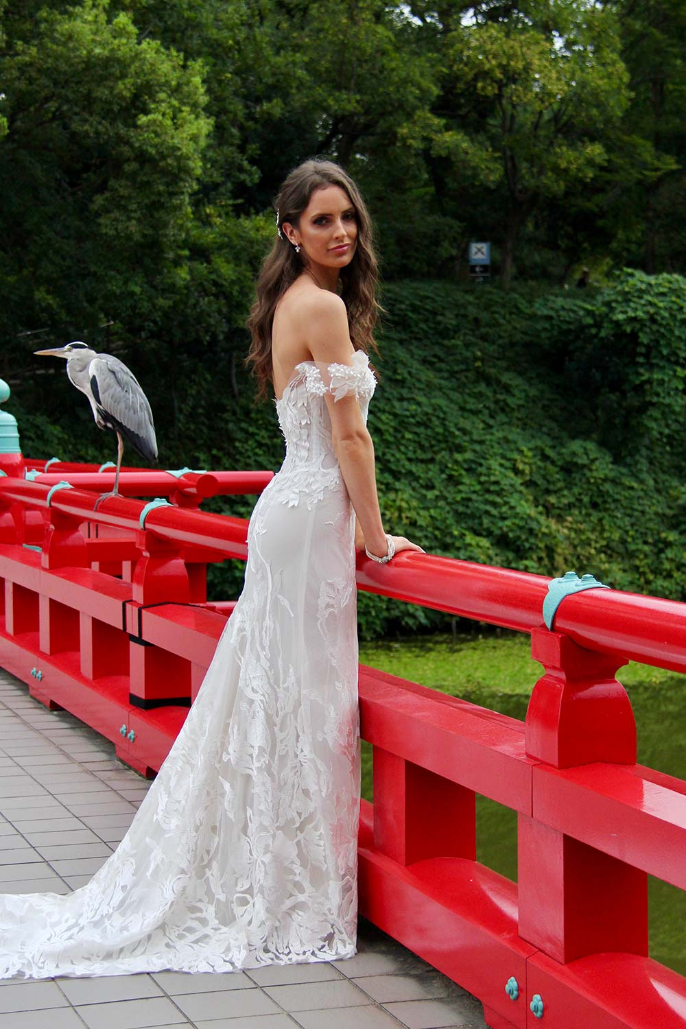 Female model wearing Vinka Design An Oriental Affair Wedding Dress. On a japanese bridge the side detail of a off-shoulder and form-fitting gown with corset-like boning.