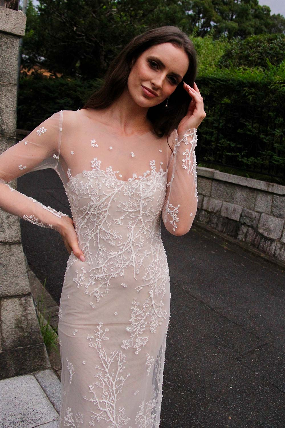 Female model wearing Vinka Design An Oriental Affair Wedding Dress. On the stairs to a japanese temple the front detail of a form-fitting, semi-sheer gown with a high neckline and fully beaded blossom lace gown.