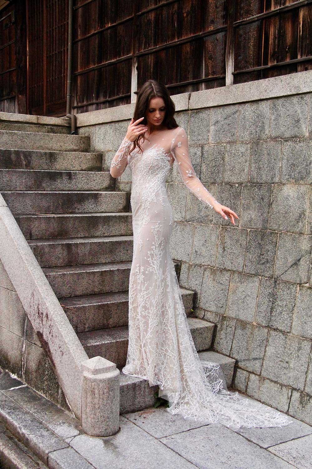 Female model wearing Vinka Design An Oriental Affair Wedding Dress. On the stairs to a japanese temple the side detail of a form-fitting, semi-sheer gown with a high neckline and fully beaded blossom lace gown.