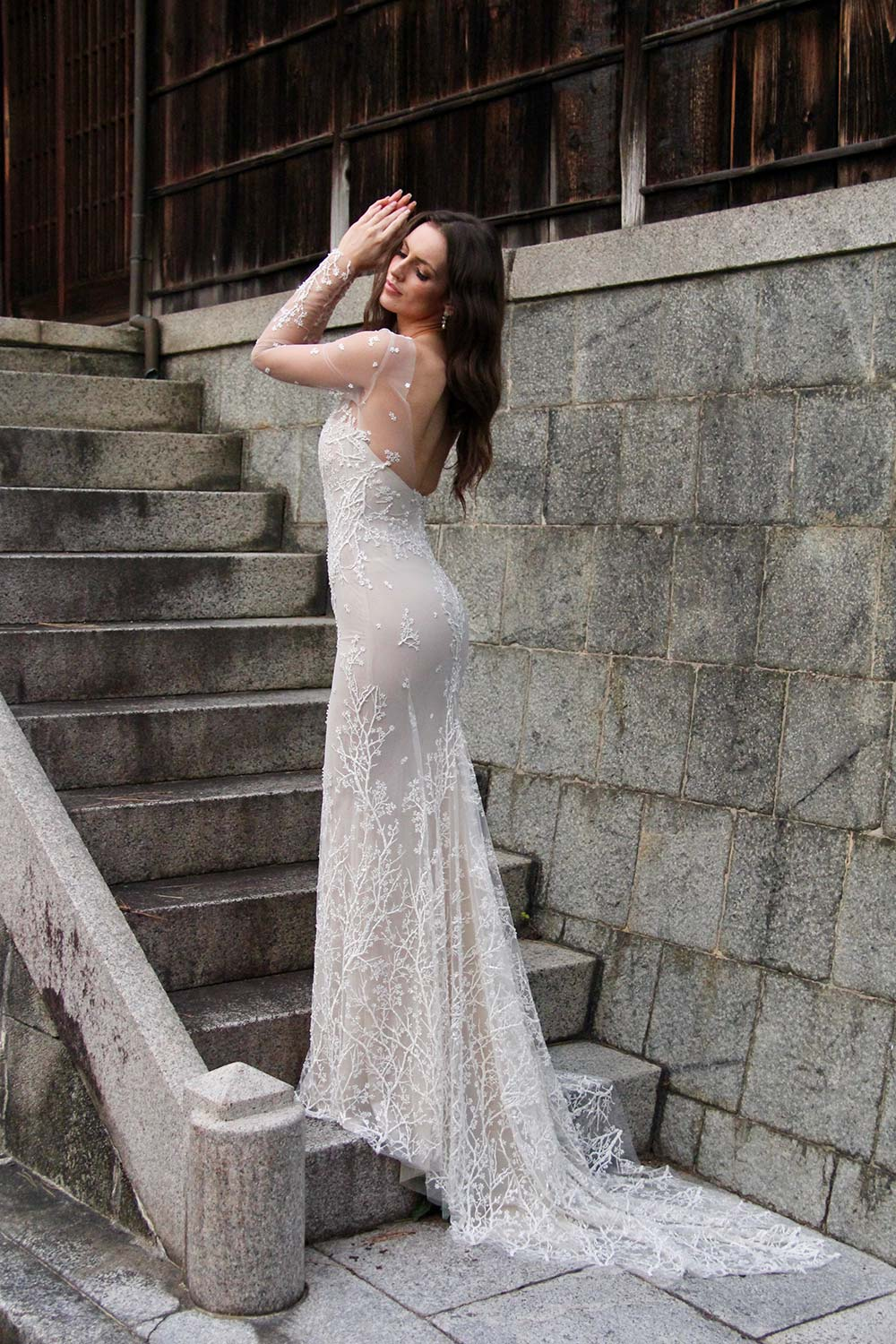 Female model wearing Vinka Design An Oriental Affair Wedding Dress. On the stairs to a japanese temple the back detail of a form-fitting, semi-sheer gown with a high neckline and fully beaded blossom lace gown.