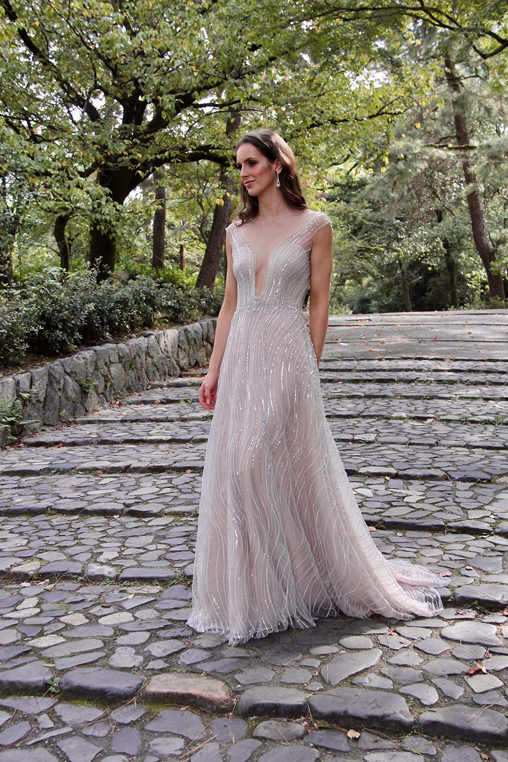Female model wearing Vinka Design An Oriental Affair Wedding Dress. On a walkway in the japanese forest the front detail of a high illusion neckline with a richly beaded silver-lined bodice and low sheer lace back on a blush base.