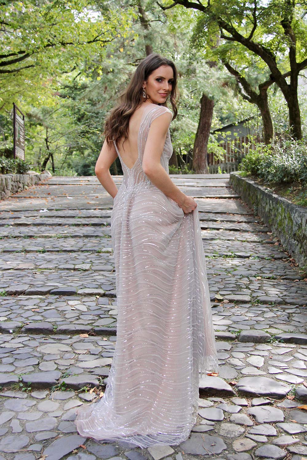 Female model wearing Vinka Design An Oriental Affair Wedding Dress. On a walkway in the japanese forest the back detail of a high illusion neckline with a richly beaded silver-lined bodice and low sheer lace back on a blush base.