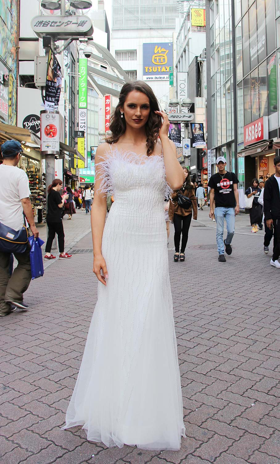 Female model wearing Vinka Design An Oriental Affair Wedding Dress. On a busy Japanese street the front detail of a bodice with thin spaghetti straps and a low back beading and a tulle panel skirt.