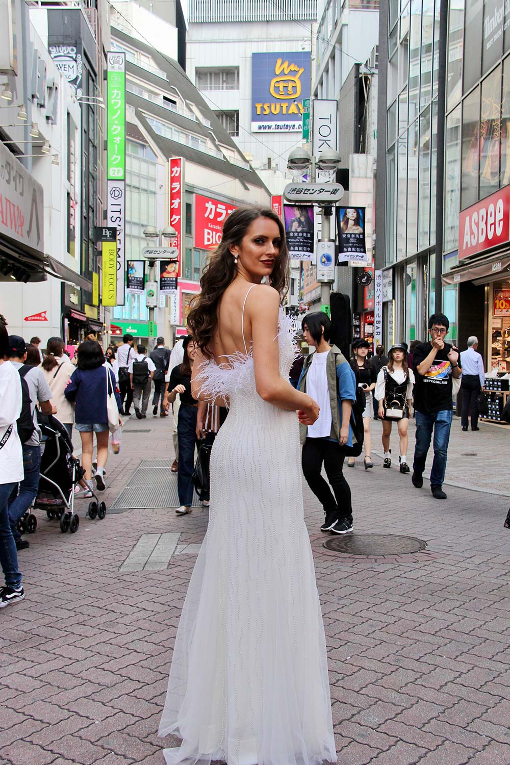 Female model wearing Vinka Design An Oriental Affair Wedding Dress. On a busy Japanese street the back detail of a bodice with thin spaghetti straps and a low back beading and a tulle panel skirt.