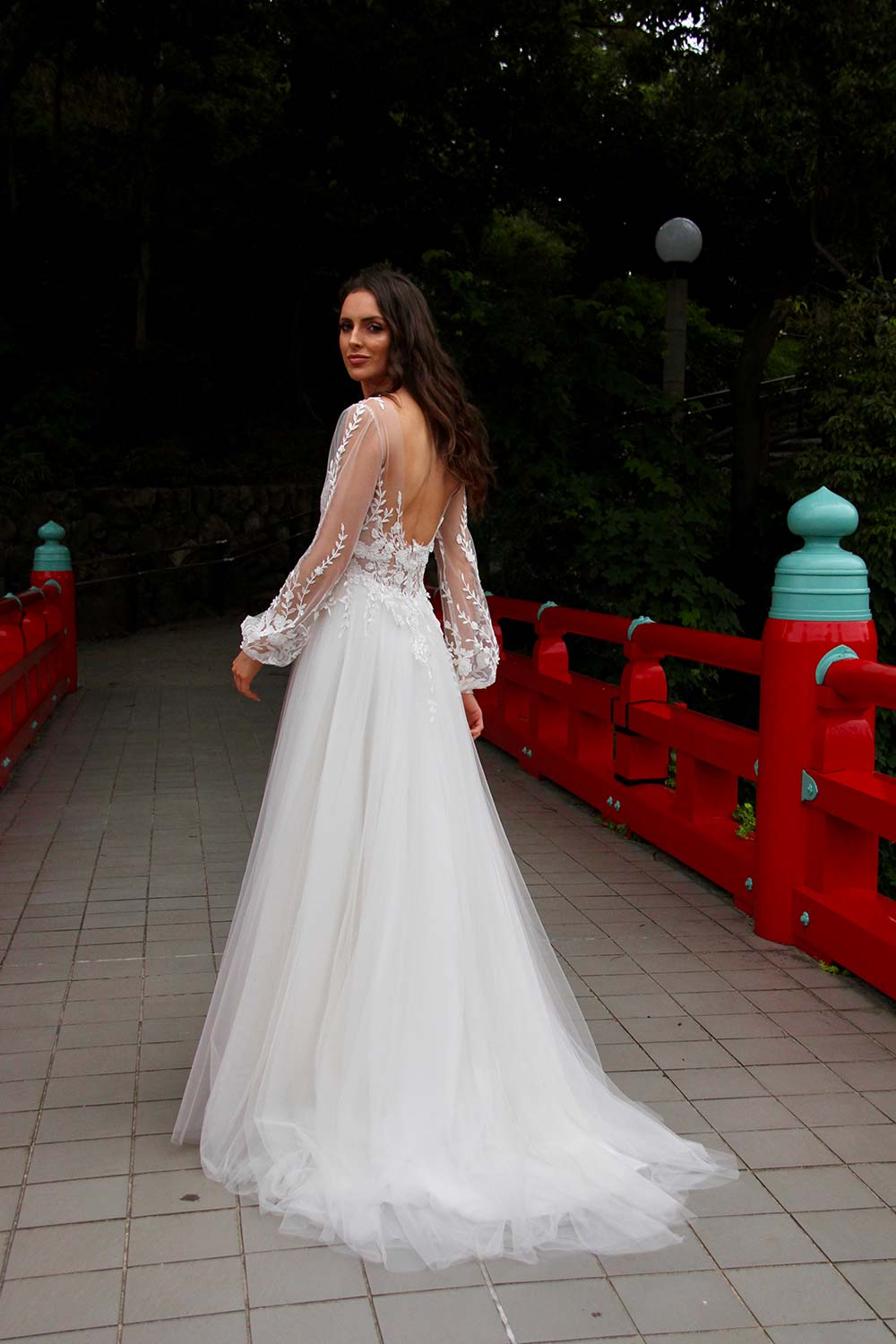 Female model wearing Vinka Design An Oriental Affair Wedding Dress. On a Japanese bridge the back detail of a semi-sheer base and three-dimensional ivory leaf and flower lace with soft tulle skirt.