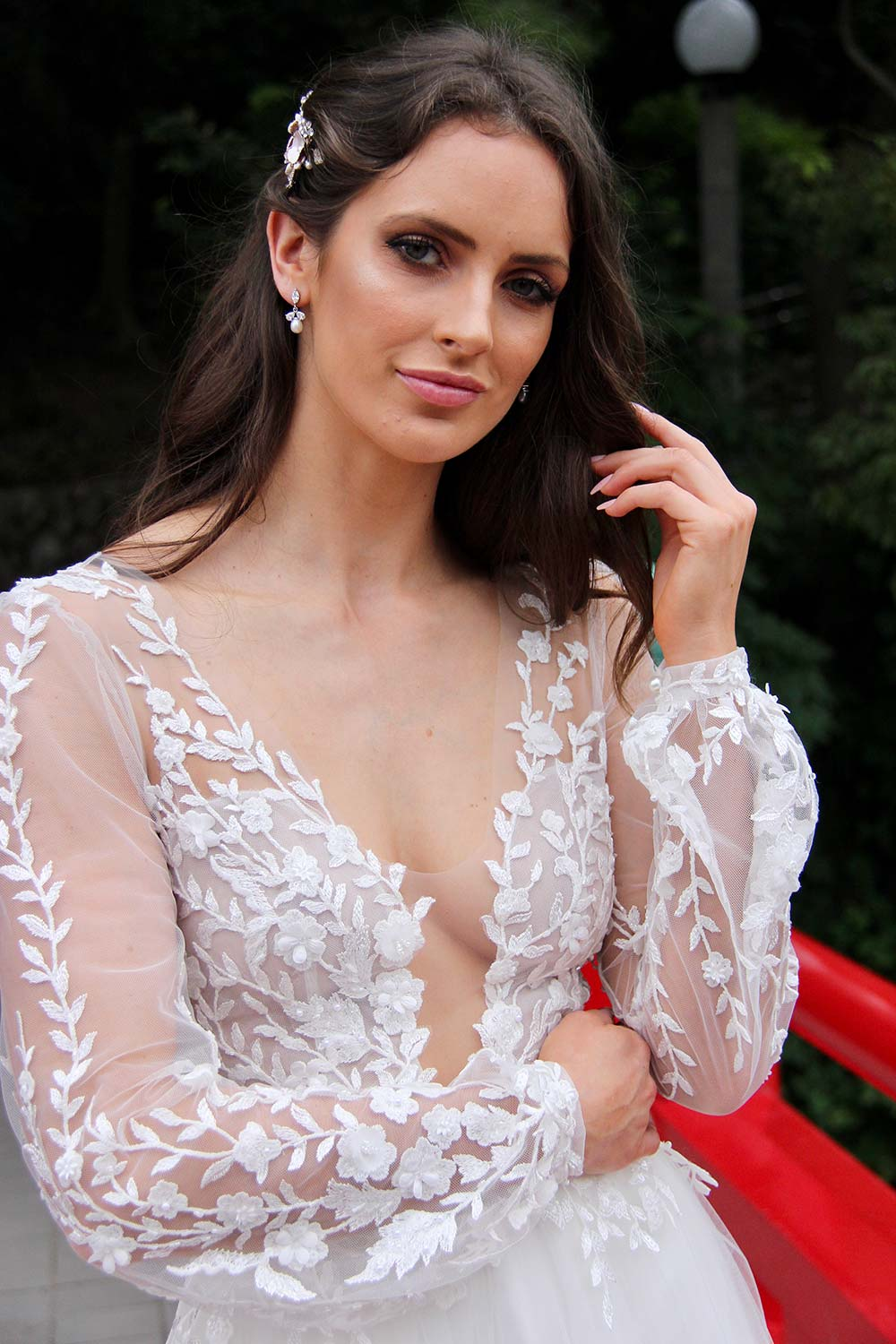 Female model wearing Vinka Design An Oriental Affair Wedding Dress. On a Japanese bridge the front detail of a semi-sheer base and three-dimensional ivory leaf and flower lace with soft tulle skirt.