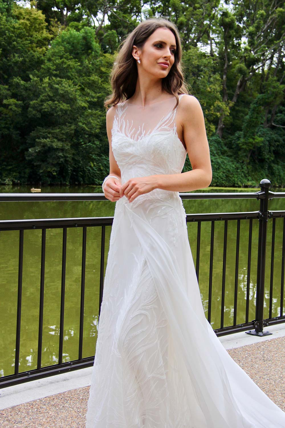 Female model wearing Vinka Design An Oriental Affair Wedding Dress. On a Japanese walkway the font detail of a a high sheer neckline with a fitted, structured bodice double-strapped low back