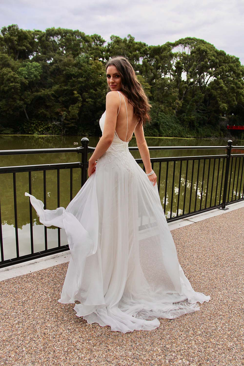 Female model wearing Vinka Design An Oriental Affair Wedding Dress. On a Japanese walkway the back detail of a a high sheer neckline with a fitted, structured bodice double-strapped low back