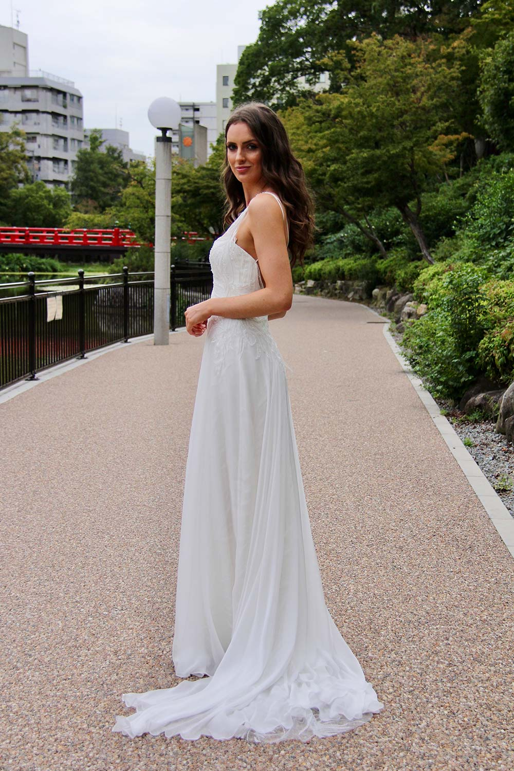 Female model wearing Vinka Design An Oriental Affair Wedding Dress. On a Japanese walkway the side detail of a a high sheer neckline with a fitted, structured bodice double-strapped low back
