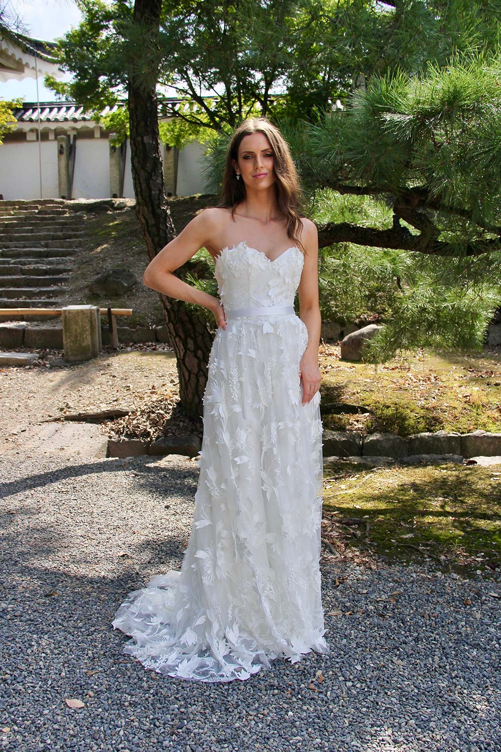 Female model wearing Vinka Design An Oriental Affair Wedding Dress. In sunlit garden the front detail of a boned fitted strapless bodice and leaf lace on a tulle base