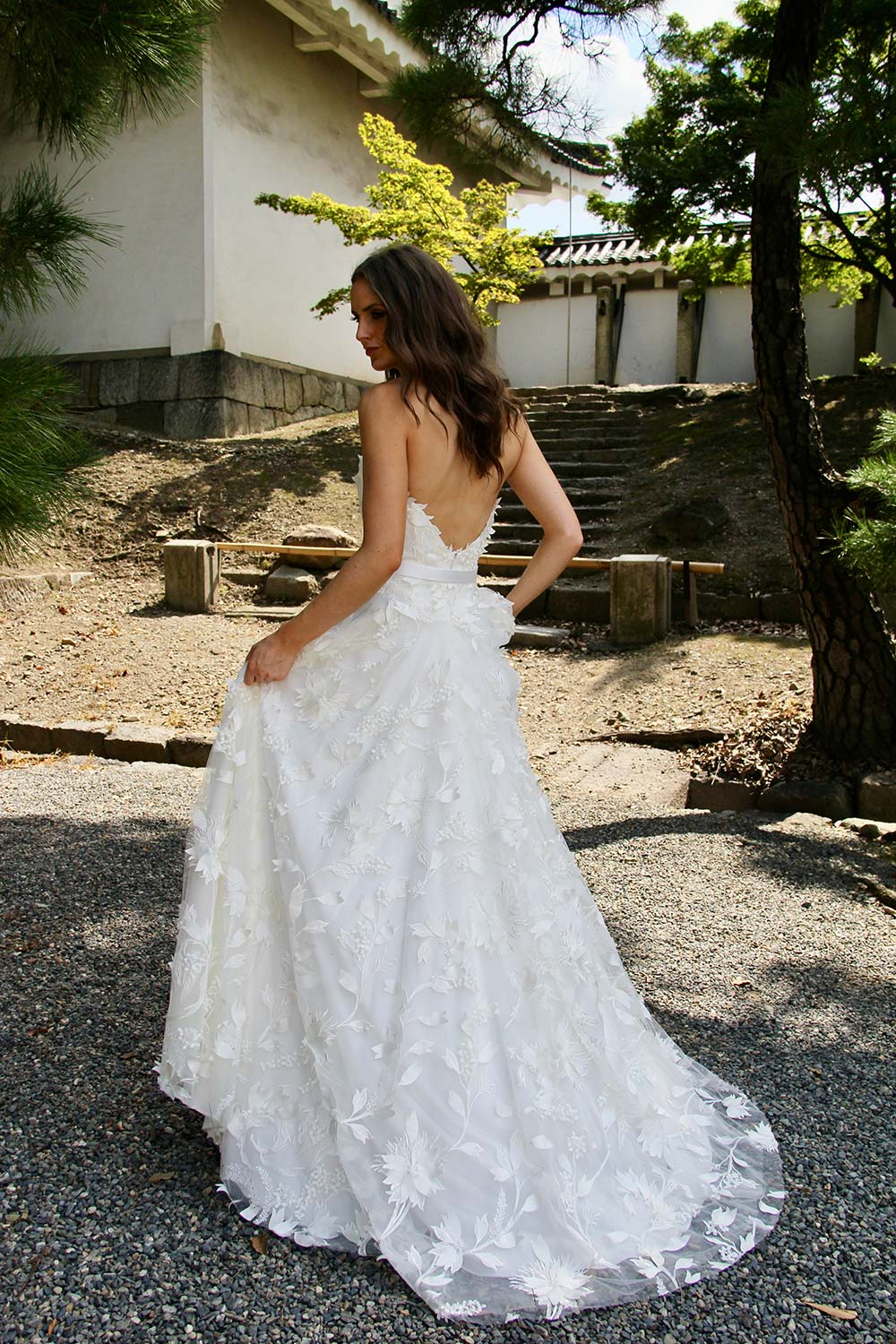 Female model wearing Vinka Design An Oriental Affair Wedding Dress. In sunlit garden the back detail of a boned fitted strapless bodice and leaf lace on a tulle base