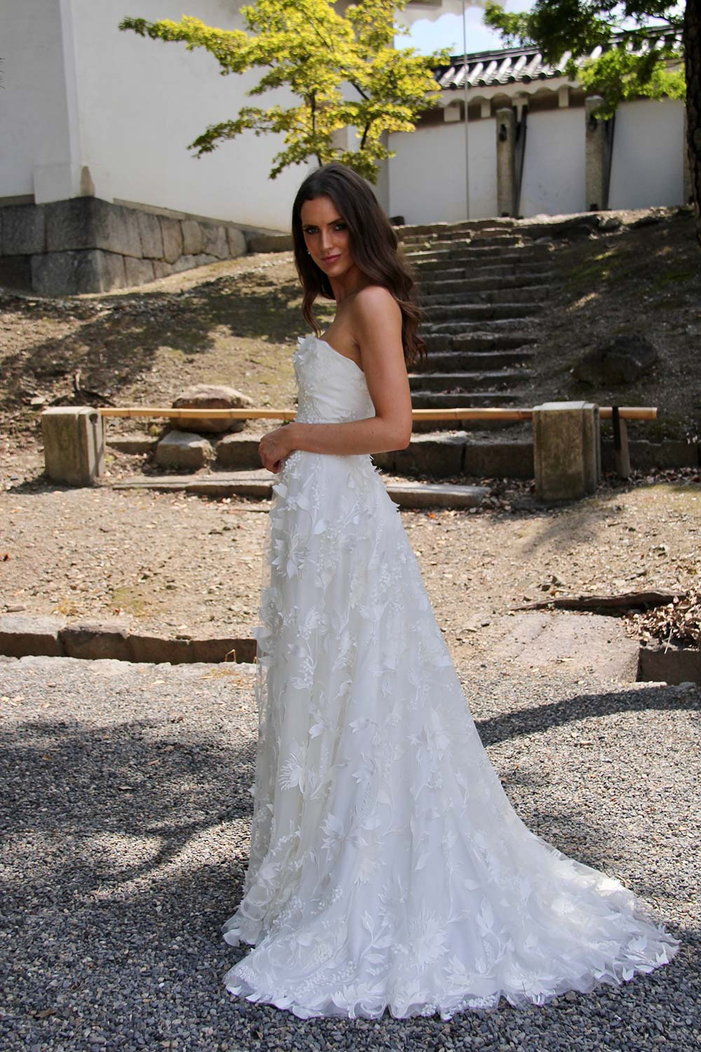 Female model wearing Vinka Design An Oriental Affair Wedding Dress. In sunlit garden the side detail of a boned fitted strapless bodice and leaf lace on a tulle base