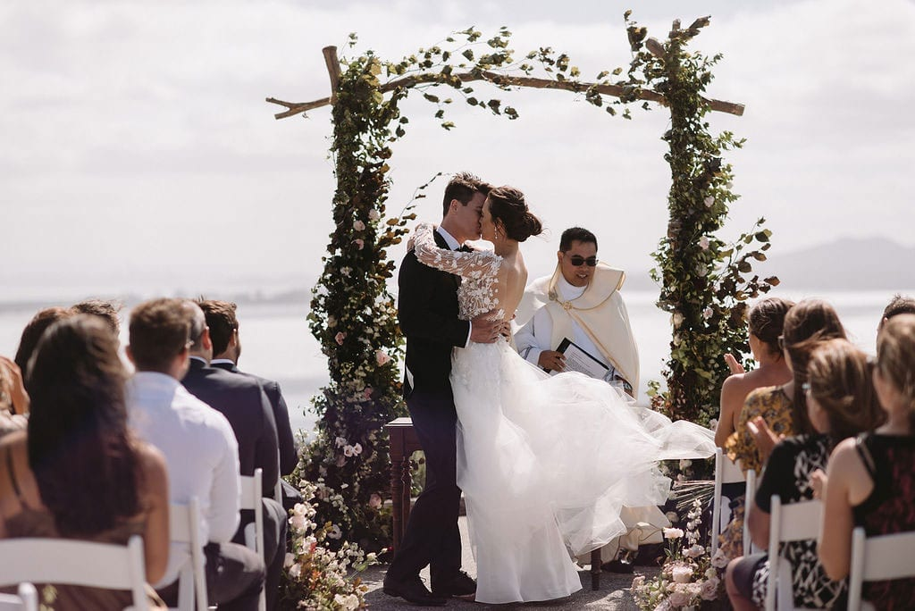 Vinka Design Features Real Weddings - bride and groom kiss under flower archway. Bride in custom made wedding gown with a whimsical tulle overskirt that had lace flowers appliqued and trailing into the train.