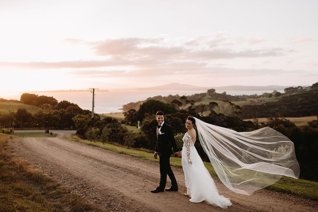 Vinka Design Features Real Weddings - bride in custom made wedding dress with gown featured a whimsical tulle overskirt that had lace flowers appliqued and trailing into the train. Walking along road with groom.