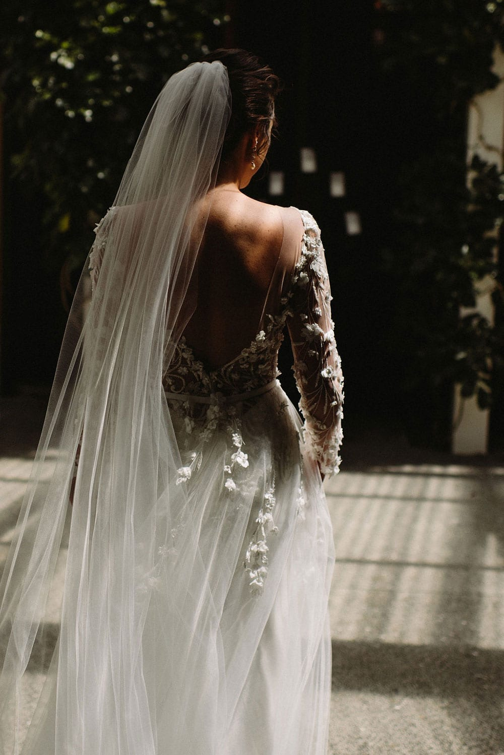 Vinka Design Features Real Weddings - bride in custom made wedding dress with tulle overskirt with appliqued lace flowers and custom made veil in dappled sunlight from behind