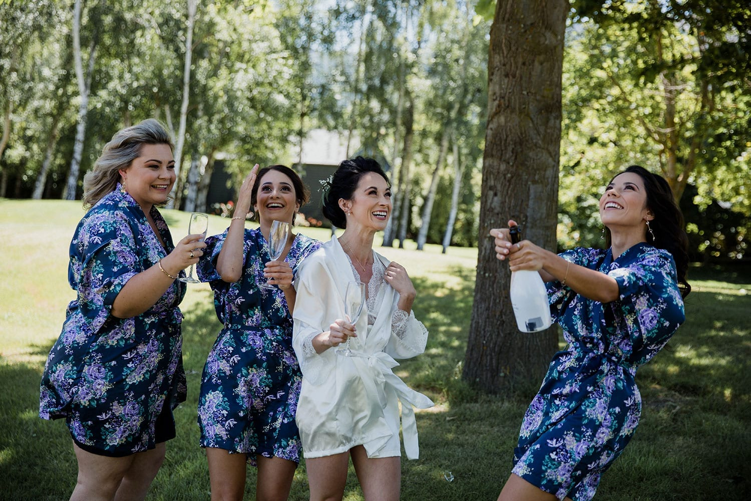 Vinka Design Features Real Weddings - Bride on wedding morning in silk dressing gown with bridesmaids popping champagne outside