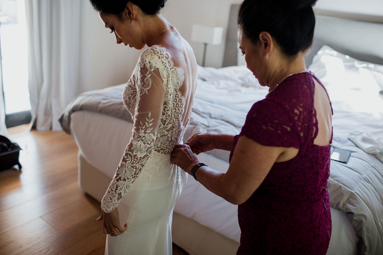Vinka Design Features Real Weddings - Bride in bespoke custom made wedding gown being fastened at back