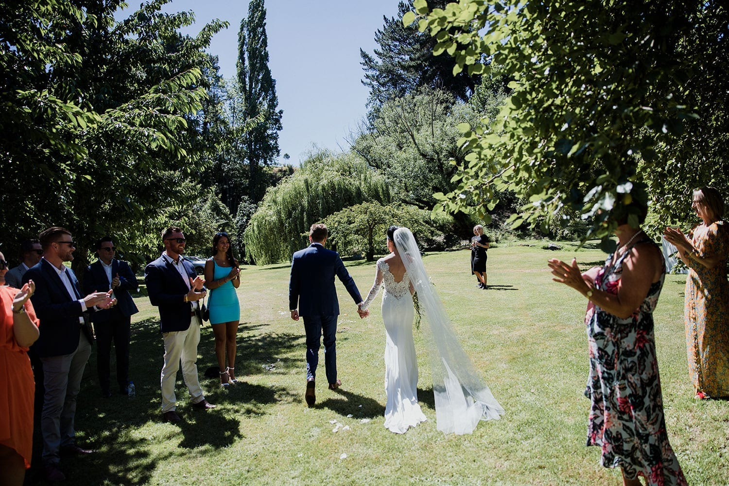 Vinka Design Features Real Weddings - bride in bespoke custom made gown with veil and train following behind with groom leaving ceremony