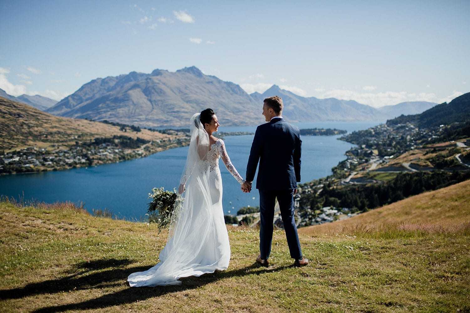 Vinka Design Features Real Weddings - bride in bespoke custom made gown with groom looking over Queenstown lake from fields