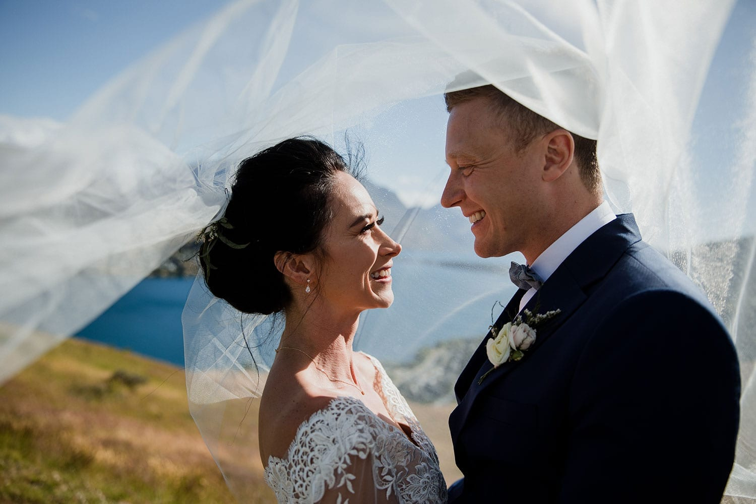 Vinka Design Features Real Weddings - bride in bespoke custom made gown with groom under veil in breeze with Queenstown lake in background
