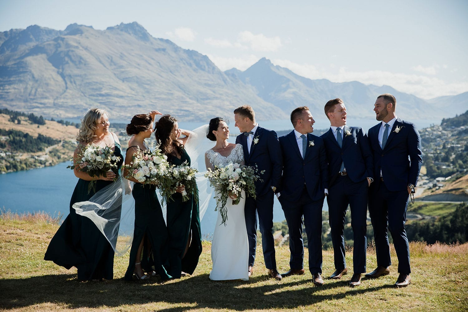 Vinka Design Features Real Weddings - bride in bespoke custom made gown with groom and bridal party with Queenstown with mountains in background