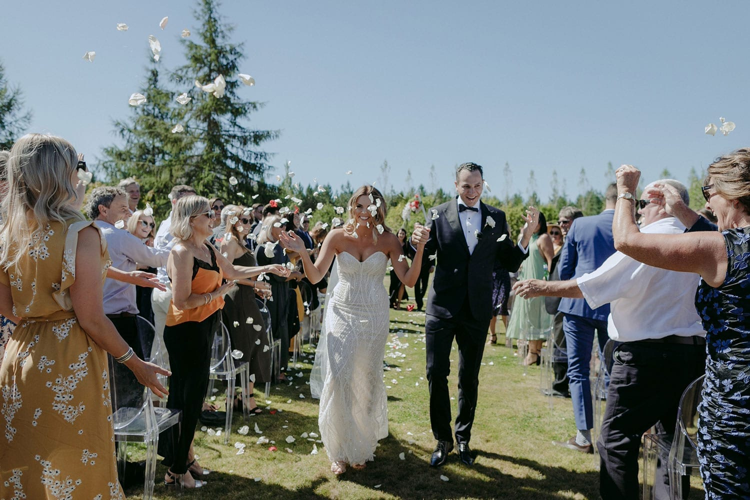 Vinka Design Features Real Weddings - bride in custom made gown, a combination of our Indi wedding dress with added beading appliqued and sewn by hand, over the top of a nude semi sheer base. With groom and confetti walking down aisle