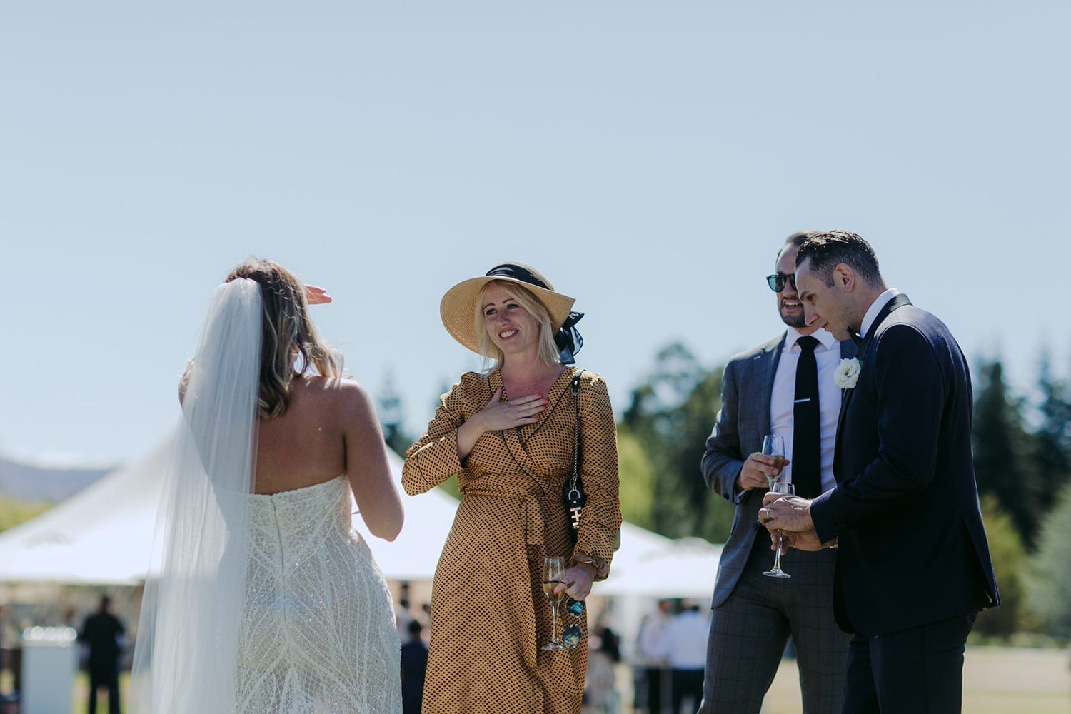 Vinka Design Features Real Weddings - bride in custom made gown, a combination of our Indi wedding dress with added beading appliqued and sewn by hand, over the top of a nude semi sheer base. With guests outdoors