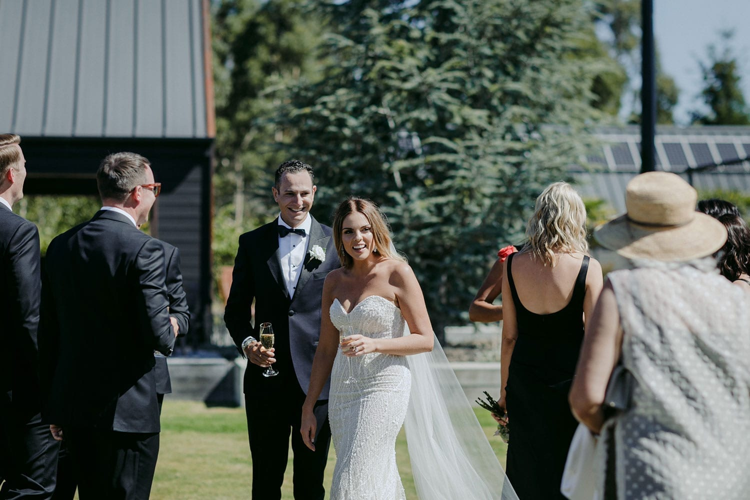 Vinka Design Features Real Weddings - bride in custom made gown, a combination of our Indi wedding dress with added beading appliqued and sewn by hand, over the top of a nude semi sheer base. With guests outdoors in sunlight